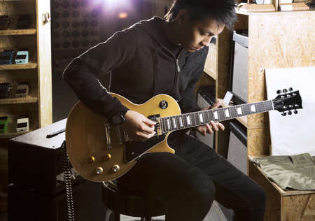 アジア 10 代の若者のエレク トリック ギター、後ろから輝くスポット ライトと一緒に遊んで。