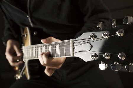 Nahaufnahme von einem Junge spielt eine Gitarre.