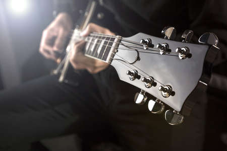 young musician: Close up of a man playing a guitar with spot light behind.