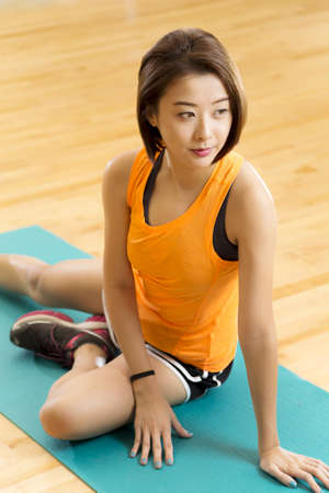 An Asian lady doing her warm up stretching exercise in a gym photo