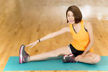 warm up: An Asian lady doing her warm up stretching exercise by reaching to her feet in a gym Stock Photo