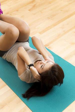 Vertikale Schuss von einer asiatischen Dame tut ihr sit ups trainieren in einem Fitnessstudio. Lizenzfreie Bilder