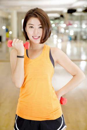Eine asiatische Dame tun Gewichtheben Übung in einem Fitnessstudio.