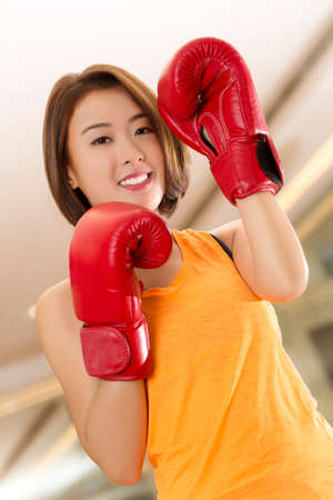 thai boxing: An Asian lady in boxing pose in a gym  Stock Photo