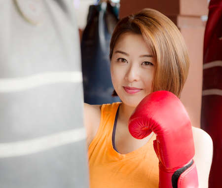 An Asian lady waring red glove practicing boxing  photo