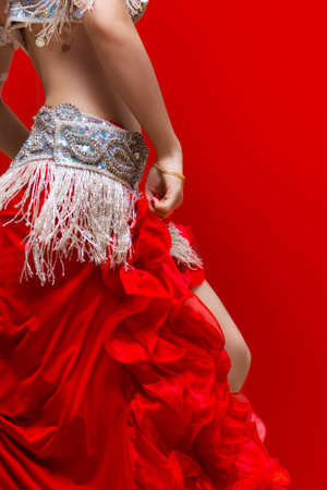 An Elegance red dress Belly dancer girl in action  With Red background photo