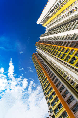 hdb: An extreme low angle shot of a new colorful high rise apartment against the sky