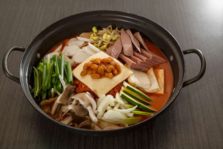 A heated wok of korean food with sliced ham, sausages and vermicelli- Budae Jeongol photo