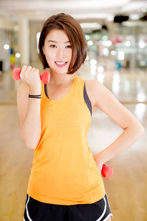An Asian lady doing weight lifting exercise in a gym. Stock Photo
