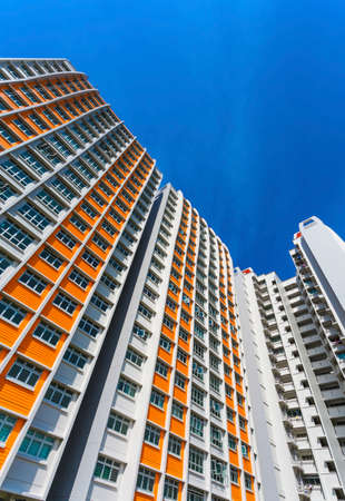 A vertical low angle shot of a new colorful high rise apartment against the sky  photo