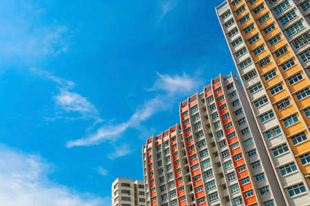 A low angle shot of a new colorful high rise apartment against the sky