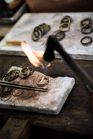 Jeweler crafting golden rings with flame torch.