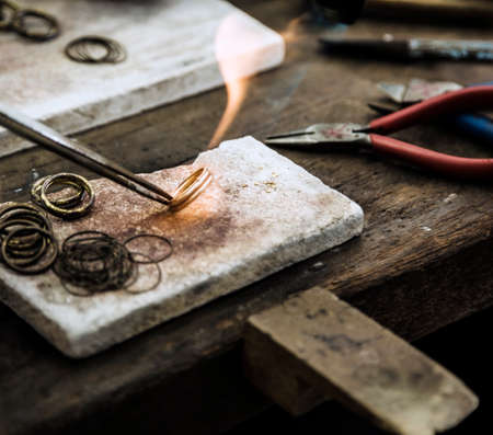 ring of fire: Close up of Jeweler crafting golden rings with flame torch. Stock Photo
