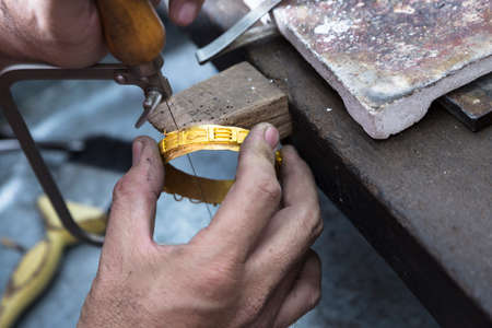 craftsmanship: Close up of Jeweler crafting golden bangle with flame torch. Stock Photo