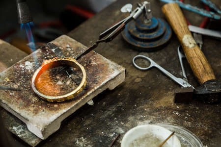 jeweller: Close up of Jeweler crafting golden rings with flame torch. Stock Photo