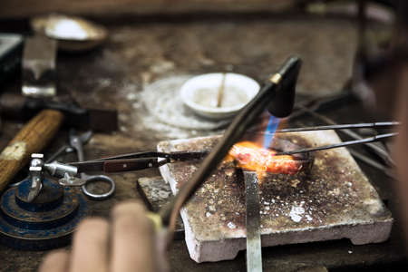 Close up of Jeweler crafting golden rings with flame torch. Stock Photo