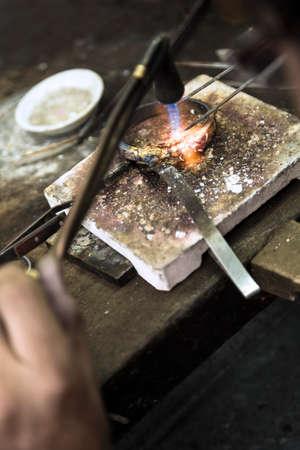 Vertikale Nahaufnahme von Juwelier Crafting goldene Ringe mit Flamme Fackel.