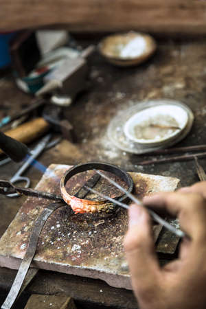 craftsmanship: Vertical close up shot of Jeweler crafting golden rings with flame torch.