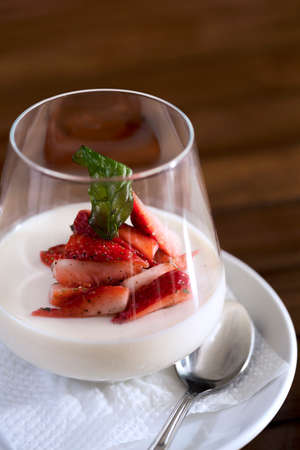 A vertical shot of a strawberry dessert in a glass ready to be served.