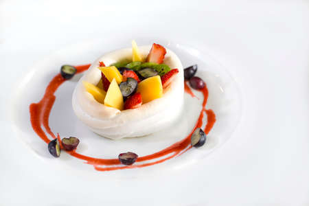 A plate of fruits dessert made of strawberries, raspberry, mango and kiwi wrap in cream isolate on white. photo