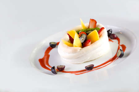 A plate of fruits dessert made of strawberries, raspberry, mango and kiwi wrap in cream isolate on white.