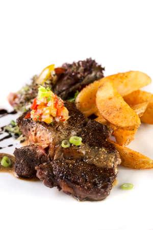 Eine vertikale Aufnahme von einem Teller mit dicken saftigen Rindersteak mit Pommes und Salat auf weißem serviert.
