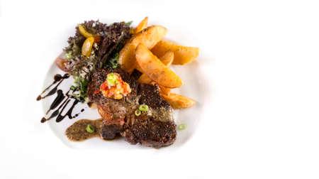 Ein Teller mit dicken saftigen Rindersteak mit Pommes und Salat auf weißem serviert werden.