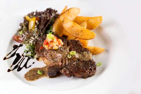 Ein Teller mit Rindersteak mit Pommes und Salat serviert.