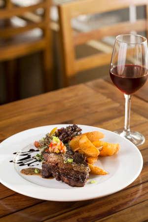 Ein Teller mit Rindersteak mit Pommes, Salat und Rotwein serviert werden