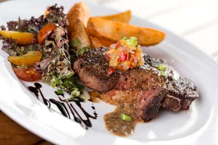 Ein Teller mit Rindersteak mit Pommes frites und Salat serviert werden.
