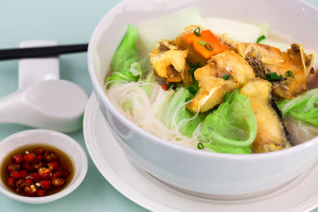 sliced: Rice noodles bee hoon noodles soup with fried fish
