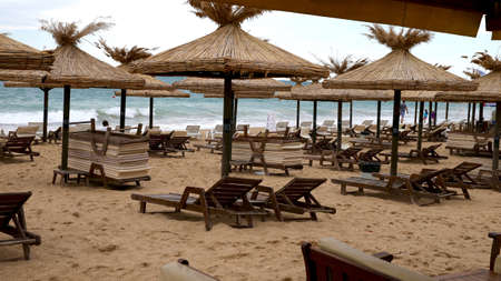 sunbeds: Sunbeds and thatched umbrellas on the beach. yellow sand and waves