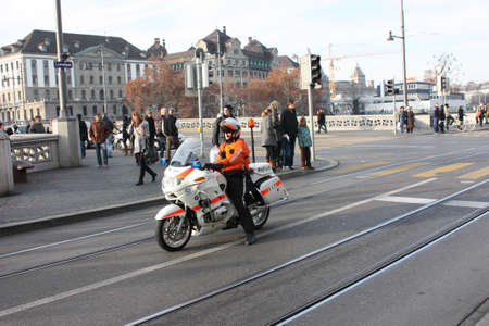 expects: Zurich, Switzerland - November 26, 2011. A police officer on a motorcycle accompanying the demo