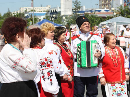 belarusian ethnicity: Tyumen, Russia - May 26 2012. Festival of national cultures Friendship Bridge. Peoples in Kazakh national dress ready for a concert. In the backyard are the presentation of the national dishes, show rituals are examples of arts and crafts, conduct master  Editorial