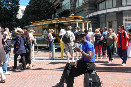 entertaining area: San Francisco, California, United States - 11 June 2010. Street musician and dancer sat on his electroacoustics relax and have a drink. People around are busy with their chores. Someone is waiting for the tram, some make photos, someone just walking. Editorial