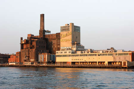 New York, NY, United States - 20 June 2010. View from Hudson on Domino Sugar Refinery. At sunset, when the sun's rays illuminate orange brown brick wall. Very old and very powerful plant for the production of sugar.