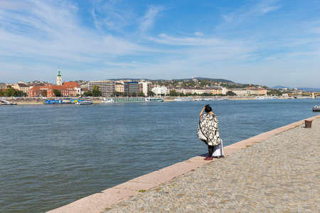 A tourist is standing with a suitcase on the waterfront. Tourists waiting for the ship. A lone tourist stands with a suitcase.
