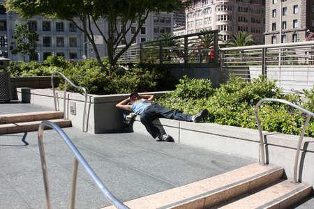 marginalized: San Francisco, USA - 11 June 2010. Homeless philosopher resting in the sun. A homeless man lying on the parapet. Homeless on the street