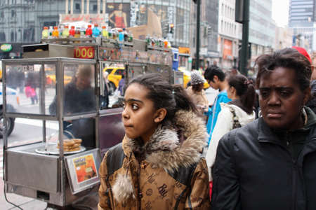 lamentable: New York, United States - 26 November 2010. Two depressed black women are on the streets of New York. Selling hot dogs in background