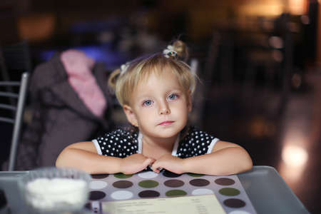 Elementary age girl sitting at the table in cafe. Girl waiting for her order. Girl is bored sitting at the table. Facial closeup portrait of a little girl in a cafe 写真素材