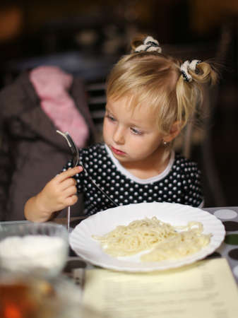 Little girl eating noodles in a cafe. Girl holding fork in hand. Elementary age girl sitting at the table in cafe. Girl is bored sitting at the table. Facial closeup portrait of a little girl in a cafe.