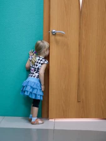 The girl looked in through the door. Girl peeping as are classes in school. The girl was late to class.