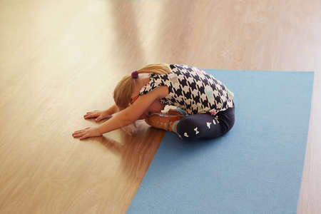Girl does stretching exercises in the gym. Girl does head tilts to the legs in the sitting position. Sports gymnastics yoga martial arts tai Chi warm up the muscles ligaments sitting exercises.
