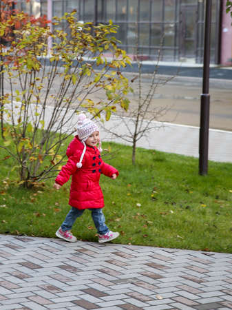 Girl marching through the Park in autumn. She is wearing red coat and hat. The girl is happy and marching through park.