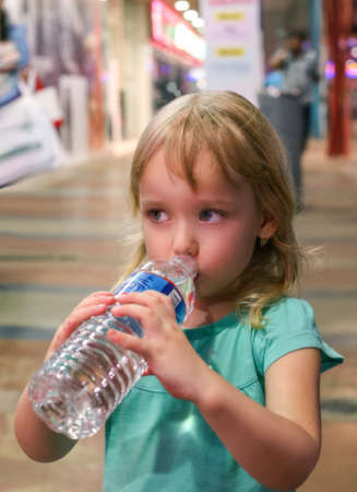 Little girl drinks water from a large bottle. The girl standing on the street drinking water from a bottle. Mineral water bottle street girl hands the summer heat outdoor.