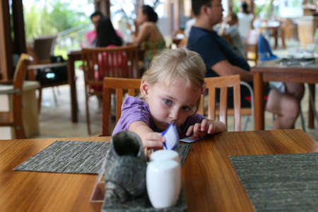 assign: Little girl reaching for a napkin. Girl sitting on a chair. The girl reached for the salt. Summer cafe the restaurant, the table is empty napkin hand girl takes get.