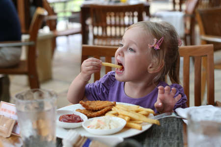 Girl eating French fries. Girl shoves in your mouth fries. The girl at the table dine in fast food. Cafe restaurant outdoors.