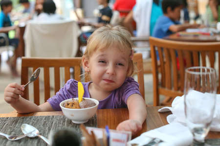 Girl eats ice cream. The girl wrinkled face. The girl in the cafe at the table. Eating ice cream with a spoon. Tart sour face.