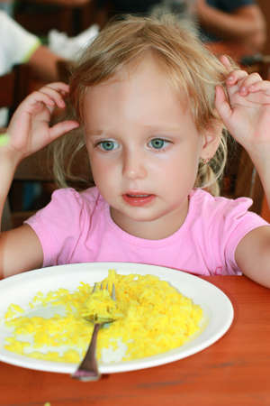 The girl ate the rice and no longer wants. The plate of rice on the table in front of the girl. Girl is looking detached gaze to the side. She doesn't want rice. Fed up. Full. 写真素材