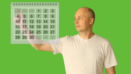 Man choice date on calendar. Planning period of month. Plan vacation season period on virtual screen. Alpha channel green screen background. Adult caucasian bald man hand finger touch virtual screen. Archivio Fotografico